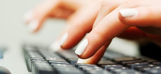 Female hands typing on the computer keyboard.